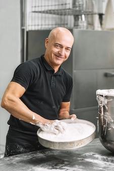 Gebakchef-kok die metaalkom met slagroom houden. concept van zoetwaren, koken desserts en keukengerei.