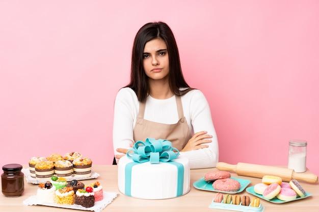 Gebakchef-kok met een grote cake in een lijst die verstoord voelen
