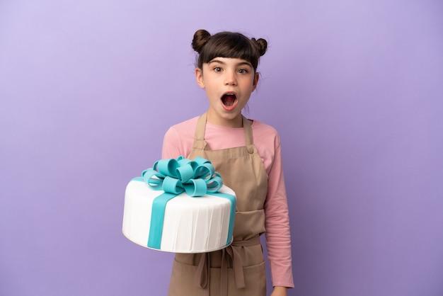 Gebakje meisje met een grote cake geïsoleerd op paars met verrassingsgelaatsuitdrukking