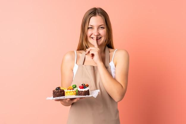 Gebakje oekraïense chef-kok die muffins houden die op roze worden geïsoleerd die stiltegebaar doen