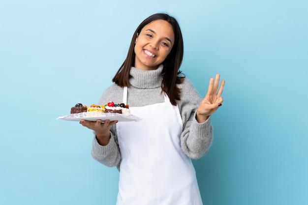 Gebakjechef-kok die een grote cake over geïsoleerd blauw gelukkig houden en drie met vingers tellen