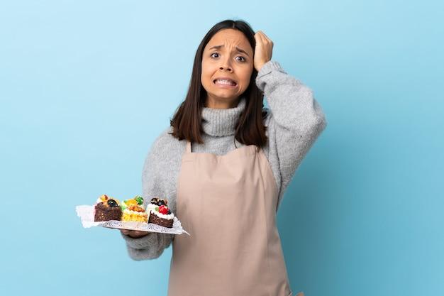 Gebakjechef-kok die een grote cake over geïsoleerde blauwe muur houden die zenuwachtig gebaar doen
