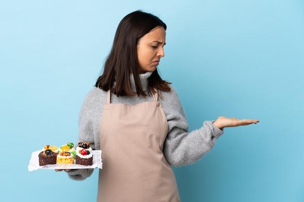 Gebakjechef-kok die een grote cake over geïsoleerde blauwe muurholding houden copyspace met twijfels