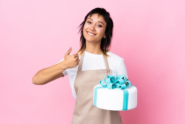 Gebakjechef-kok die een grote cake over roze muur houden die duimen op gebaar geven