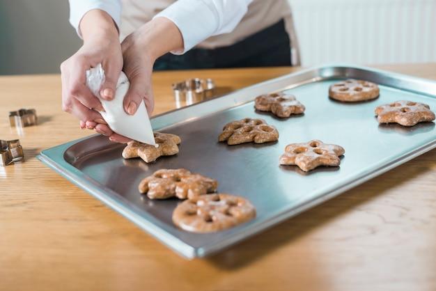 Gebakjechef-kok die heerlijke koekjes van verschillende vormen verfraaien