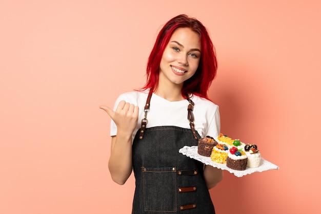 Gebakjechef-kok die muffins houden die op roze muur met duimen op gebaar en het glimlachen worden geïsoleerd
