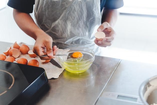 Gebakjechef-kok gescheiden dooier van wit ei in glaskom voor het koken van cake.