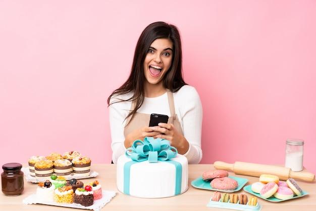 Gebakjechef-kok met een grote cake in een lijst over geïsoleerde roze verrast muur en het verzenden van een bericht