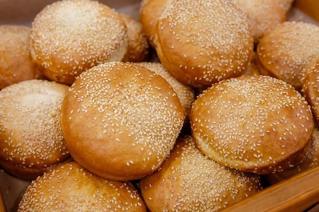 Gebakjes, sesambroodjes op plank of vitrine in bakkerij of winkel