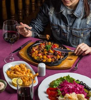 Gebakken aardappel en champignons op een houten bord