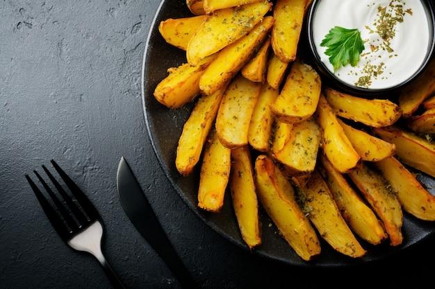 Gebakken aardappel met greens en saus in zwarte ceramische schotel op donkere concrete of ceramische lijst. selectieve aandacht. bovenaanzicht. plaats voor tekst.