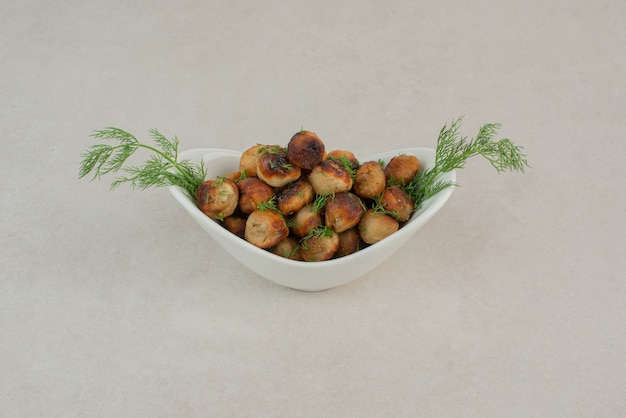 Gebakken aardappel met greens op witte plaat.
