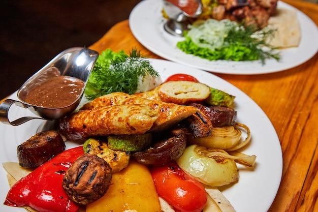 Gebakken aardappelen en gegrilde groenten met spiesjes en worstjes