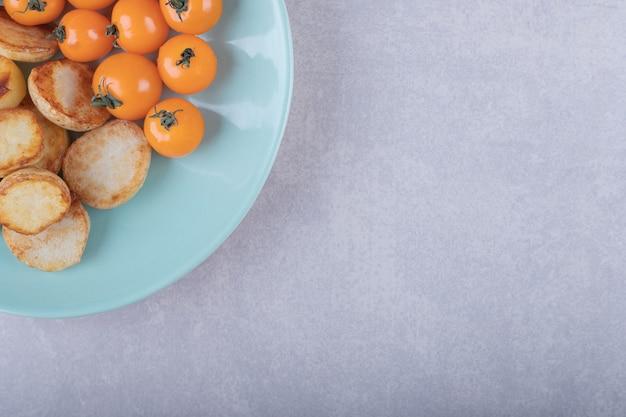 Gebakken aardappelen en kerstomaatjes op blauw bord.