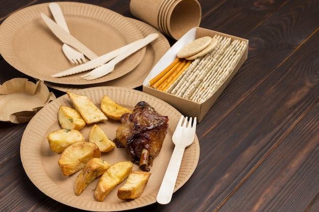 Gebakken aardappelen en kip in milieuvriendelijke kartonnen wegwerpschaaltjes. donkere houten achtergrond. bovenaanzicht. kopieer ruimte