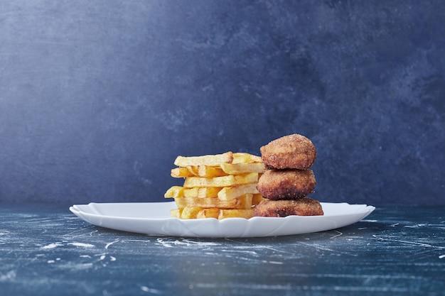 Gebakken aardappelen en nuggets in een witte plaat.