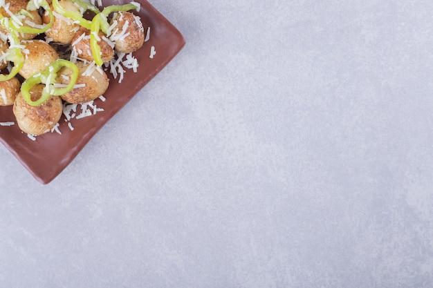 Gebakken aardappelen en peper plakjes op bruine plaat.