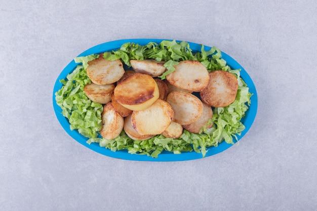 Gebakken aardappelen en sla op blauw bord.