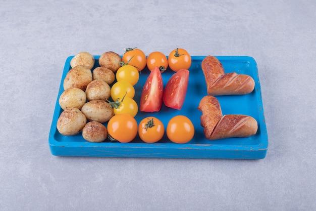 Gebakken aardappelen en worstjes op blauw bord.