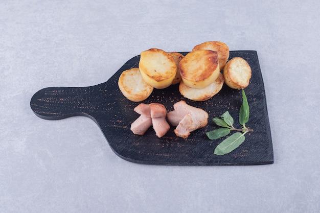 Gebakken aardappelen en worstjes op zwart bord.