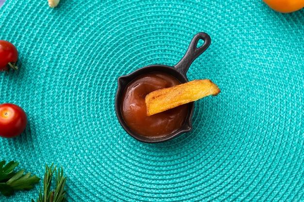 Gebakken aardappelen gedoopt in ketchup op een turquoise achtergrond. er zijn verschillende groenten in de buurt - tomaten, kruiden.