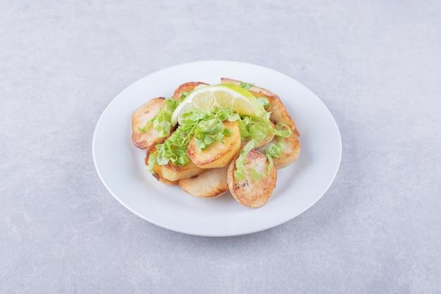 Gebakken aardappelen gegarneerd met citroen op witte plaat.
