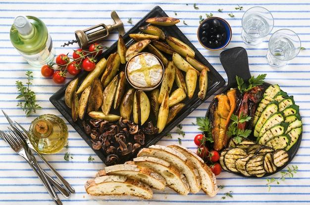 Gebakken aardappelen in de oven met camembert kaas en gegrilde groenten op tafel met witte wijn, vers brood en aromatische kruiden. zomer menu
