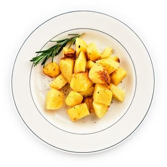 Gebakken aardappelen in de schil met rozemarijn op een witte plaat.