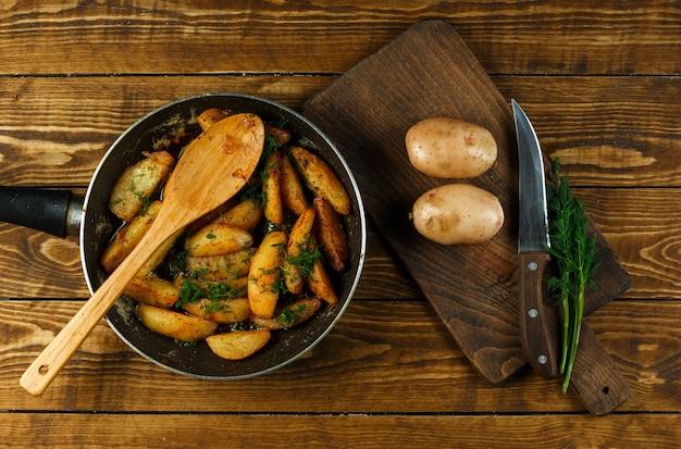 Gebakken aardappelen in een koekenpan met rauwe aardappelen en dille