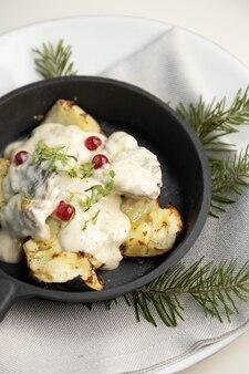 Gebakken aardappelen in een koekenpan met roomjus en bessen close-up aardappelen gebakken in kolen