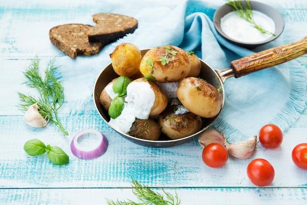 Gebakken aardappelen in een pan met zure room op rustieke ruimte
