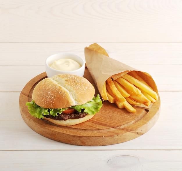 Gebakken aardappelen in een papieren zak, kaassaus en hamburger