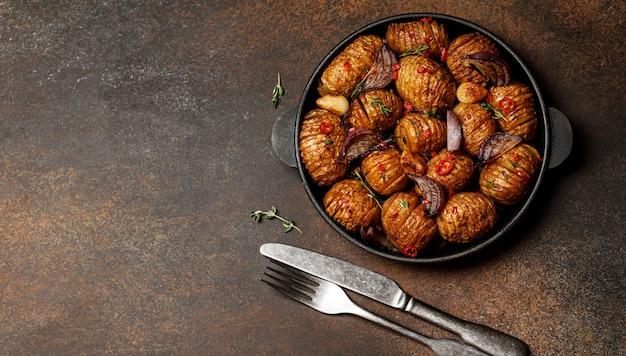 Gebakken aardappelen in gietijzeren pan met ui, knoflook en kruiden