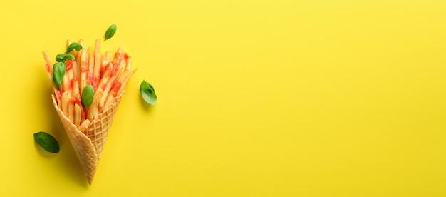 Gebakken aardappelen in wafel kegels op geel