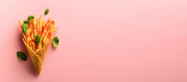 Gebakken aardappelen in wafel kegels op roze