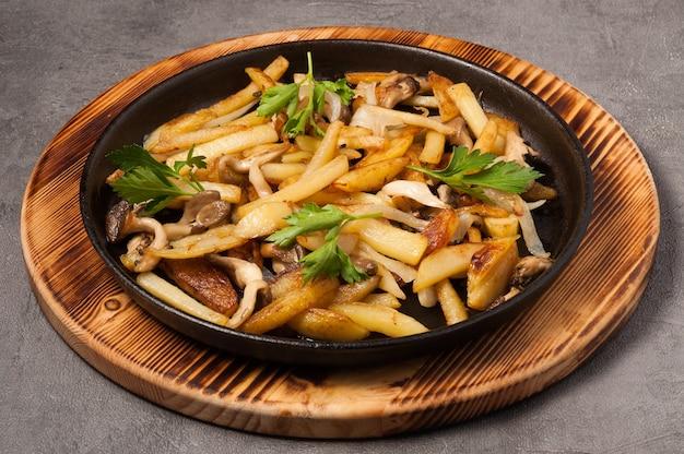 Gebakken aardappelen met bospaddenstoelen in een koekenpan