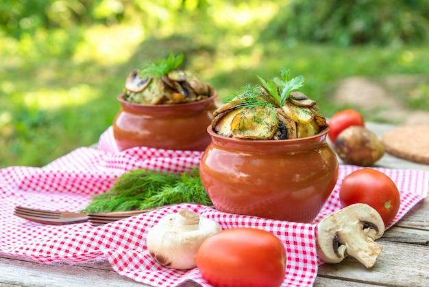 Gebakken aardappelen met champignons en diverse kruiden. in kleipotten. vegetarisch.