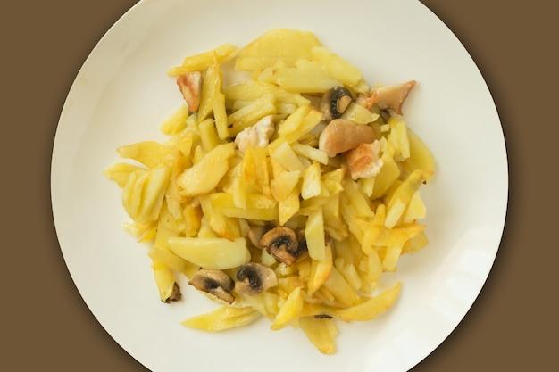 Gebakken aardappelen met champignons en kip op een witte plaat. traditionele dagelijkse maaltijd van moderne russische keuken