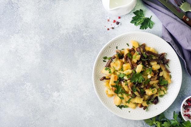 Gebakken aardappelen met champignons en verse kruiden. kopieer ruimte