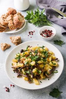 Gebakken aardappelen met champignons en verse kruiden.
