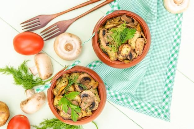 Gebakken aardappelen met champignons in de oven in een aarden pot. op een lichtgroene achtergrond. bovenaanzicht.