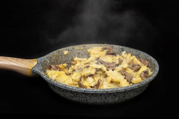 Gebakken aardappelen met champignons in een pan met grijze vlekken op een zwarte tafel, net gekookt, stoom van frituren, donkere achtergrond