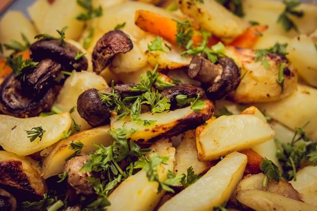 Gebakken aardappelen met champignons op witte plaat.