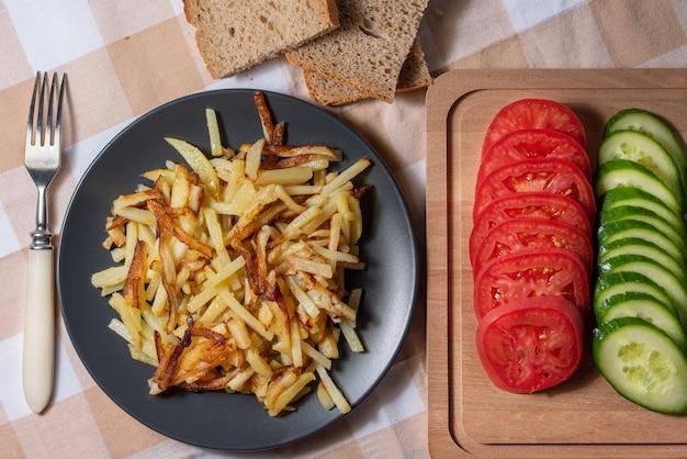 Gebakken aardappelen met een krokant korstje met brood en gesneden groenten bovenaanzicht