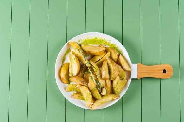 Gebakken aardappelen met groene saus en rozemarijn op een witte plaat in de vorm van een koekenpan. gebakken aardappelen met pestosaus op een groene tafel.