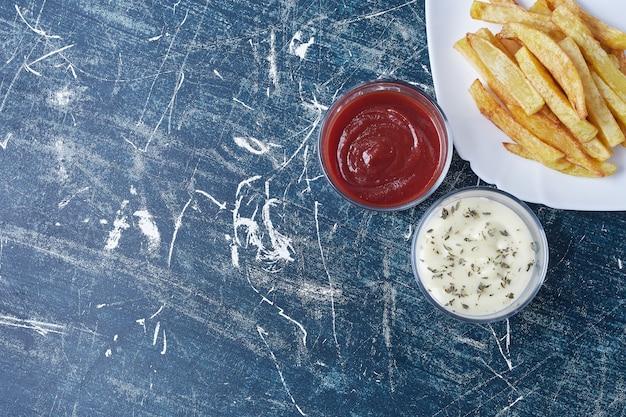 Gebakken aardappelen met ketchup en mayonaise.