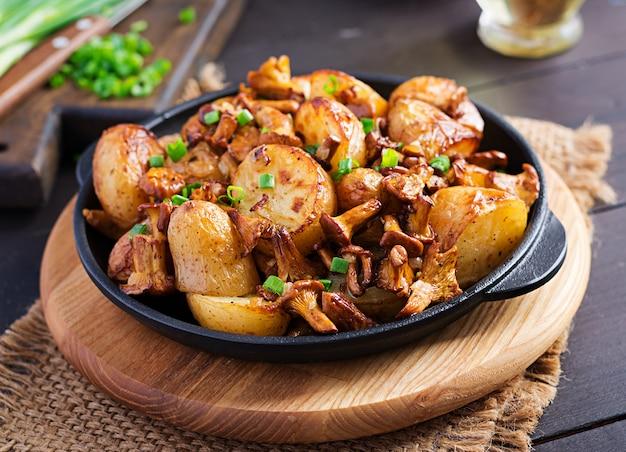 Gebakken aardappelen met knoflook, kruiden en gebakken cantharellen in een gietijzeren koekenpan.