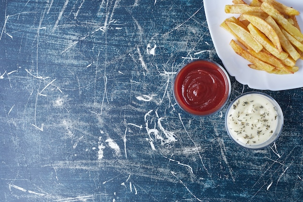 Gebakken aardappelen met mayonaise en ketchup.