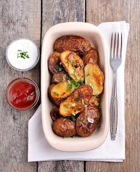 Gebakken aardappelen met sauzen op een houten bord.