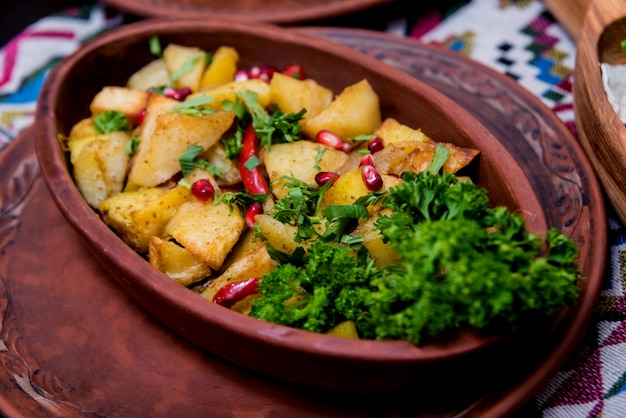 Gebakken aardappelen met stukjes vlees in een aarden pot. europese keuken.